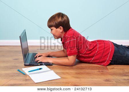 Foto eines jungen, der auf dem Boden auf seinem Laptopcomputer eingeben