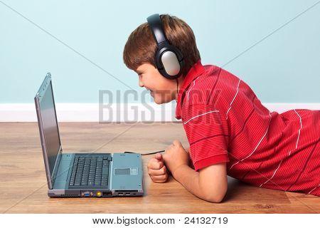 Foto eines jungen, der auf dem Boden tragen von Kopfhörern und Blick auf dem Bildschirm seines Laptops liegen