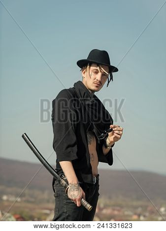 Man Face Handsome. Warrior In Black Hat, Tattooed Torso In Open Clothes. Man With Katana Sword And S