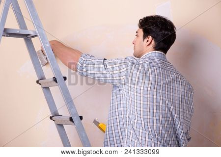 Young man applying plaster on wall at home