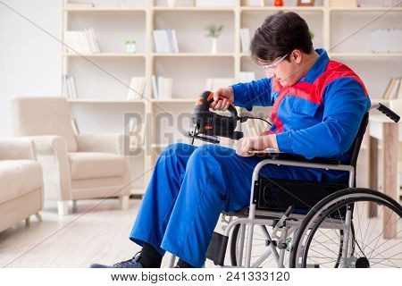 Disabled man working with handsaw at home
