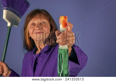 Old lady cleaner with broom on blue background. Housekeeper woman in uniform with clean spray. Cleanup and order services. Woman with long hair hold soup bottle. Cleaning and purity. poster