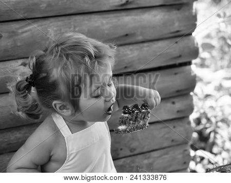 Happy Kid Having Fun. Cute Little Boy With Blond Hair Ponytail In White Pinafore Eats Fruit Cake Wit