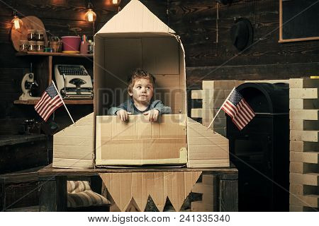 Kids Playing With Toys. Boy Play With Rocket, Cosmonaut Sit In Usa Rocket Made Out Of Cardboard Box.
