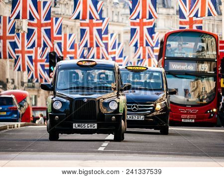London, United Kingdom - May 18, 2018: Taxi Cabs And Buses Under Union Jack Flags On Regent Street A