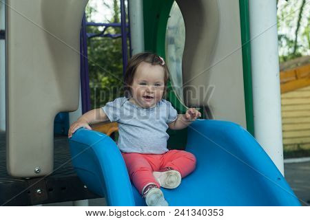 Happy Little Baby Girl Rolling Down The Hill On The Playground