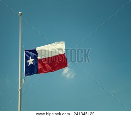 State Flag Of Texas Flying At Half-mast Or Half-staff On A Flagpole. Blue Sky Background With Copy S
