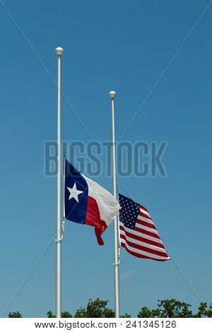 The State Flag Of Texas And The United States Flag Flying Side By Side At Half-mast Or Half-staff On