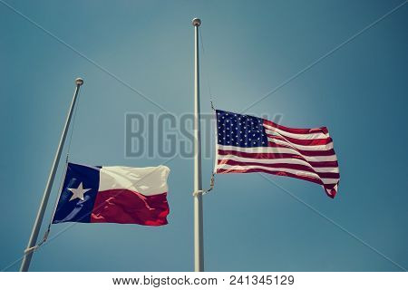 The State Flag Of Texas And The United States Flag Flying At Half-mast Or Half-staff On A Flagpole.