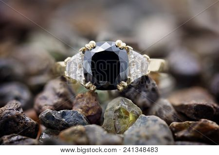 Cushion cut black diamond ring with trapezoid cut white diamonds either side, set in 18 carat yellow gold poster