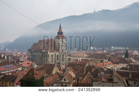 Panoramic  View Of Brasov Old Town And Black Church With The Carpathian Mountains In A Foggy Winter