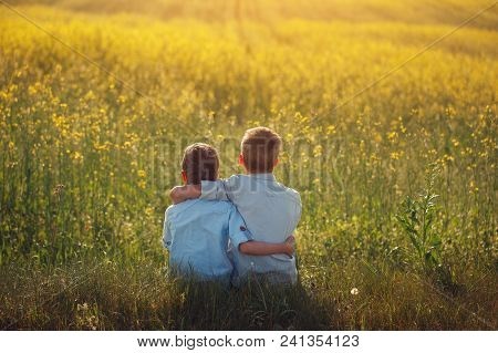 Two Little Boys Friends Holding Around The Shoulders In Sunny Summer Day. Brother Love. Concept Frie