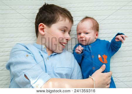 Big Brother Hugging His Newborn Baby. Toddler Kid Meeting New Sibling. Cute Boy And New Born Baby Gi