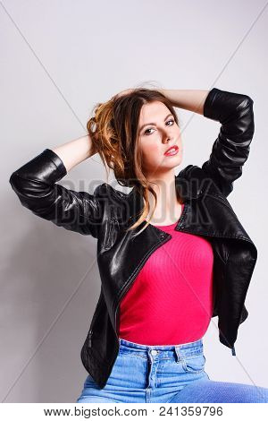 Portrait Of A Young Woman In A Black Leather Jacket And Pink Shirt Posing Collecting Hair Hands. Pun