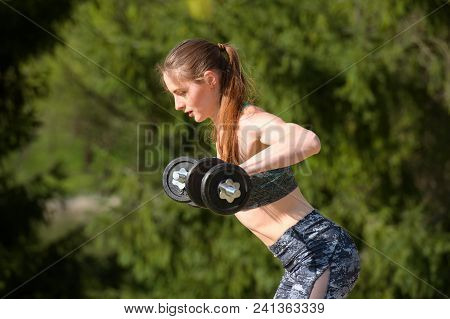 Beautiful Young Woman In Training Pumping Up Muscles Of The Back And Hands With Dumbbells. Photo Ath