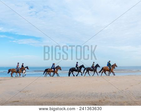 Kijkduin, The Hague, The Netherlands - May 12 2018: Group Of Horse Riders On The Beach