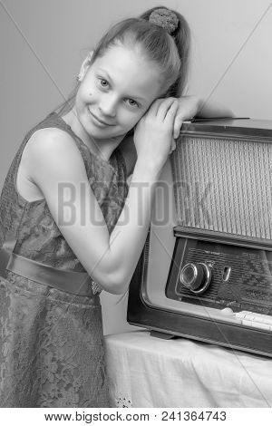 A Nice Little Girl In A Room With Furniture From The Fifties Of The Last Century, Near An Old Radio.