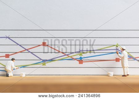 Miniature People : Worker Painting Business Graph On White Background , Business Growth Concept