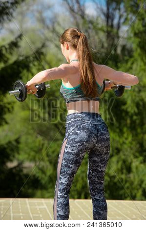 Muscular Woman Working Out With Dumbbells, Flexing Her Arm. Photo Of Sporty Woman In Sportswear. Bac