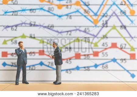 Miniature People : Businessman Standing On Business Graph Background , Business Growth Concept