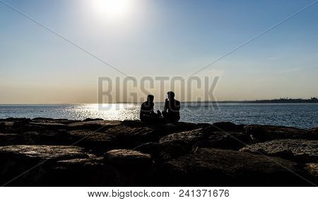 Silhouette Of People Sitting On The Sea.
