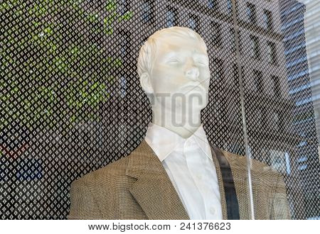 Fashion Mannequin Sitting Behind Glass On Street Side Storefront With City Sights Reflecting