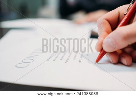 Man Hand Signing Contract Closeup. Business Partnership And Cooperation. Deal Closing And Legal Docu