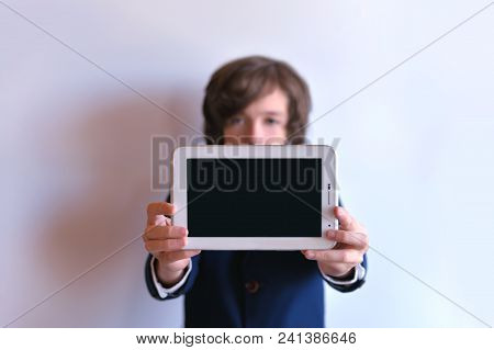 The Schoolboy Holds The Tablet On His Arms Outstretched. The Tablet Is In The Hands Of A Schoolboy.