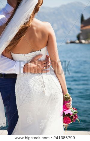 Bride And Groom Hug On View Of Sea, Mountains. Newlyweds Are After Wedding Ceremony. Bride Is Dresse