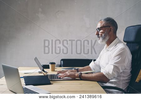 Positive Adult Businessman Using Mobile Laptop Computer While Sitting At Wooden Table At Modern Cowo