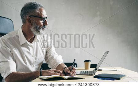 Adult Bearded Businessman Working On Mobile Laptop Computer While Sitting At Wooden Table
