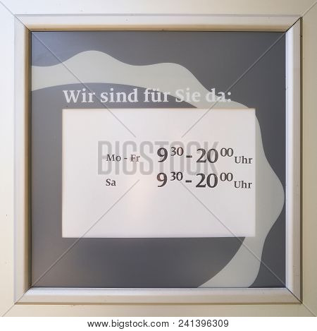 Sign With The Store Opening Times Behind The Window Of A Shop In Germany