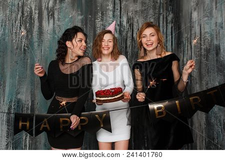 Pretty Girl With Birthday Cake And Her Friends Fooling Around And Laughing, Holding Sparklers. Horiz