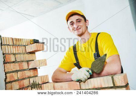 Bricklayer. Portrait of young smiling construction mason near brick wall