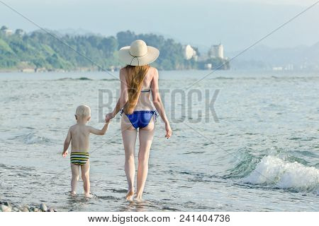 Mom And His Little Son Are Walking Along The Sea Coast. Back View