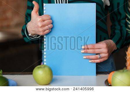 Woman Hands Showing Thumbs Up While Holding Blank Notebook On Kitchen Table Decorated With Apples. G