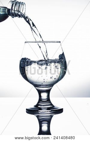 Pouring Water Into A Glass On White Background