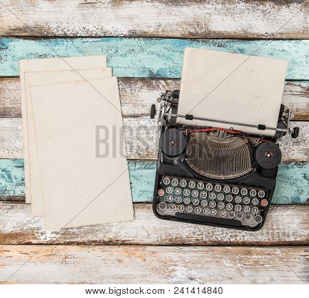 Antique Typewriter And Used Paper Sheets On Wooden Table. Flat Lay Still Life