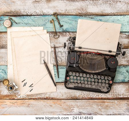Vintage Typewriter And Used Paper Sheets On Wooden Background. Flat Lay Still Life