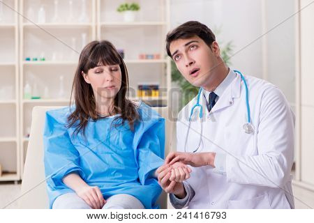 Male doctor checking up female patient in hospital