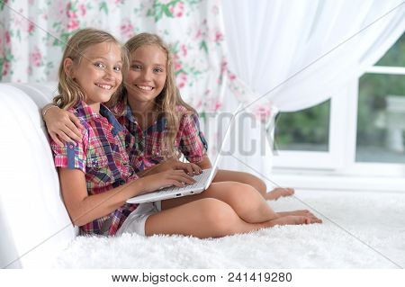 Two Adorable Twin Sisters Using Laptop At Home