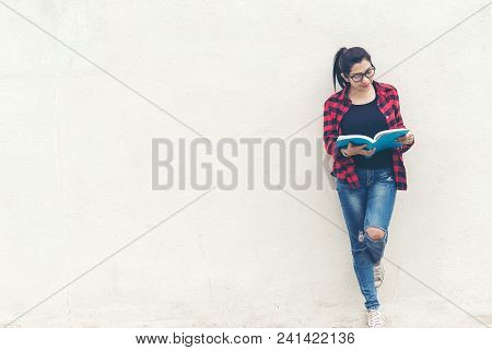 Asian Woman Standing And Holding A Book On Wall White Background.  Education Concept