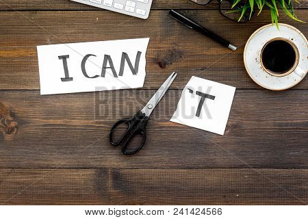 I can concept. Encourage youself. Sciccors cut off the letter t of written word I can't. Office desk. Dark wooden background top view. poster
