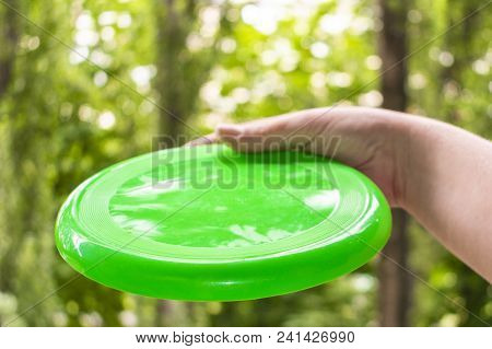 Hand Throwing A Green Frisbee Disc In The Park On A Summer Day
