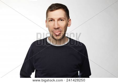 Portrait Of Handsome Young Male With Brunette Hair And Pleasant Appearance, Shows Tongue, Has Fun, W