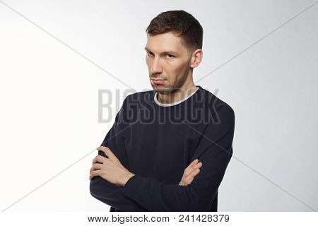 Indoor Shot Of Unhappy Young Caucasian Man Wearing Warm Sweater, Looking Strictly At Camera, Sufferi