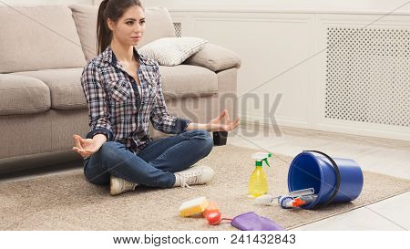 Woman Meditating, Sitting In Lotus Pose On Carpet While Cleaning Home In Living-room, Copy Space. Ho