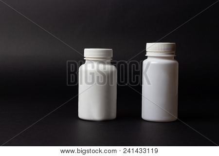 Two White Pill Bottles On Black Background. Storage Pills. Vitamins. Release Pills.