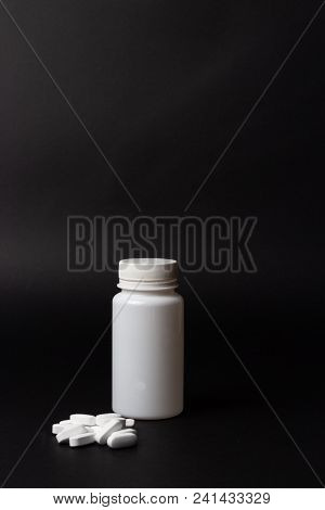 One White Pill Bottle On Black Background. Storage Pills. Vitamins. Release Pills. And White Pills,