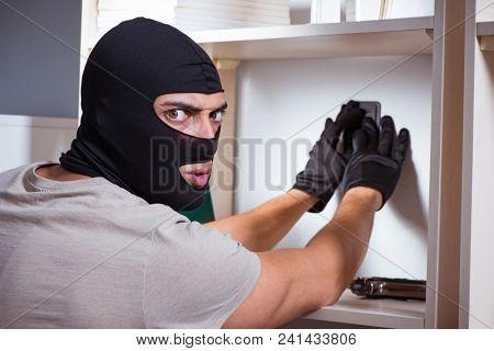 Burglar wearing balaclava mask at crime scene